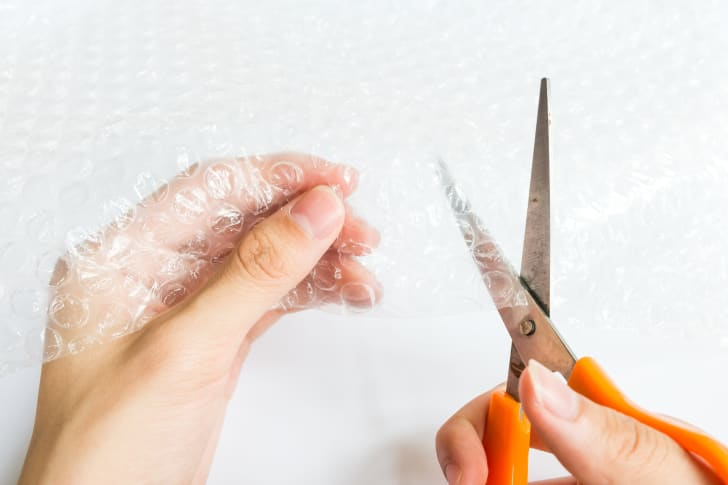 A person cutting Bubble Wrap with scissors.