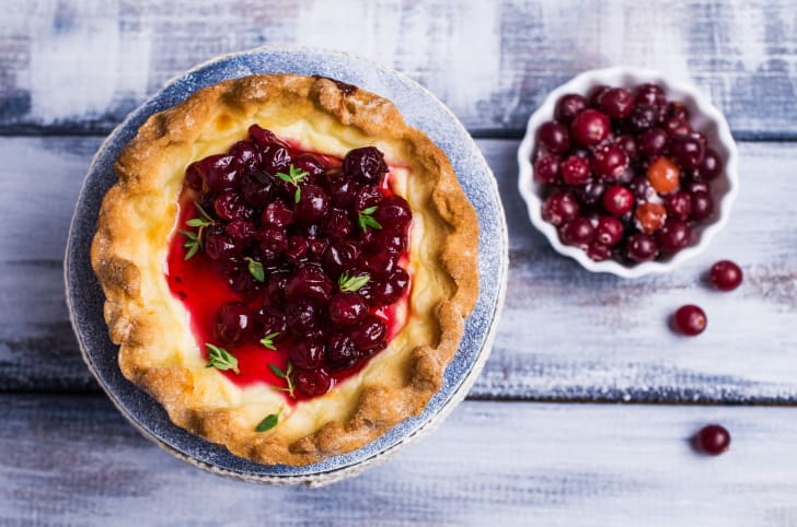 Cranberry pie with a bowl of cranberries beside it.