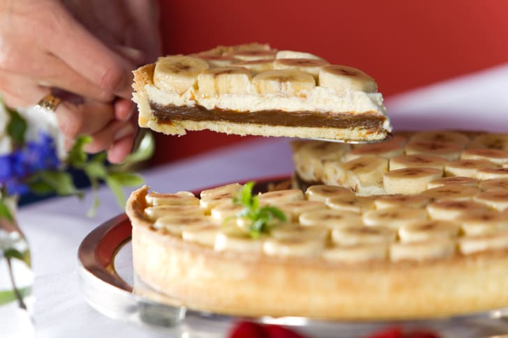 Slice of pie topped with bananas.