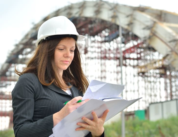 Woman in hard hat with papers.