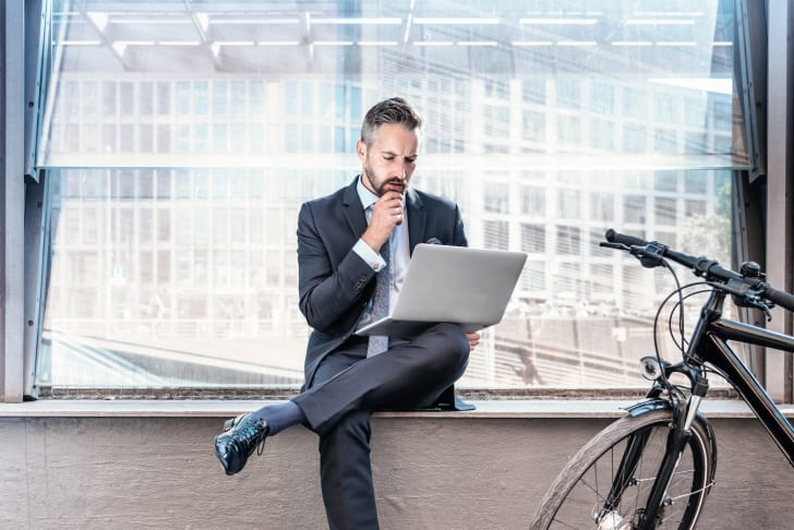 Office worker with bike on laptop.