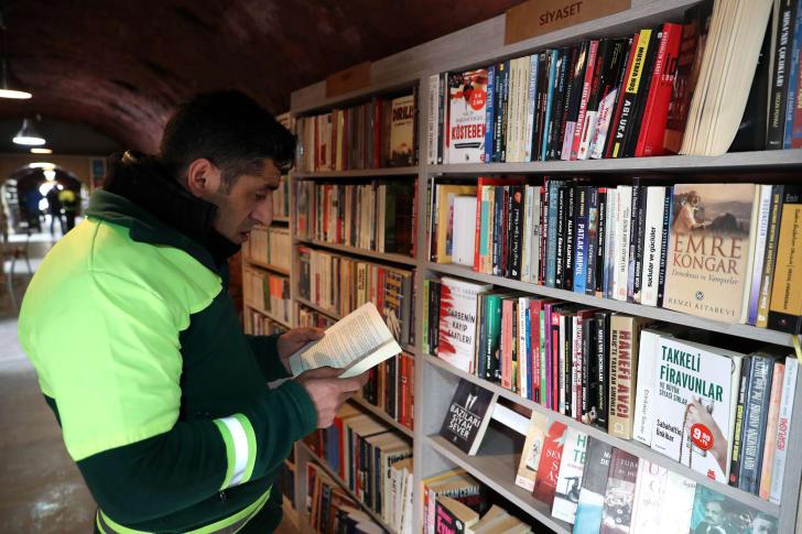 Man reading book at shelf.