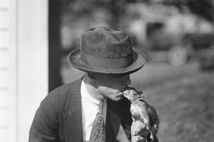 A man in a hat kisses a squirrel on the White House grounds