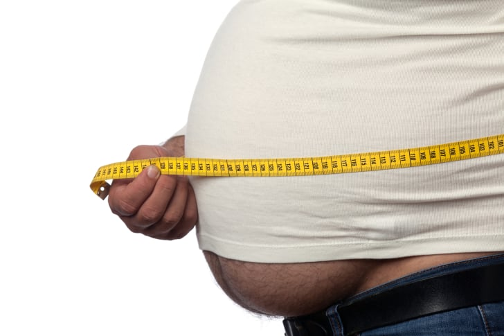 Up-close shot of an overweight man measuring his belly.