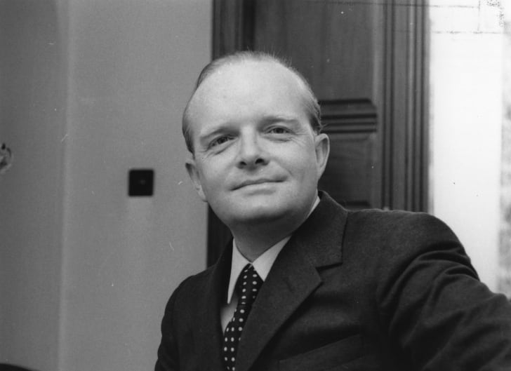 A black-and-white photo of a smiling Truman Capote