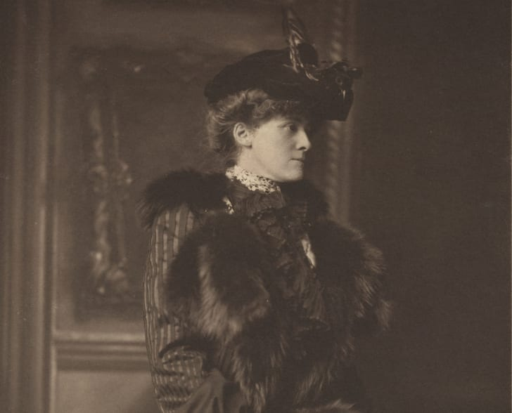 Photo of author Edith Wharton, wearing hat with a feather, coat with fur trim, and a fur muff