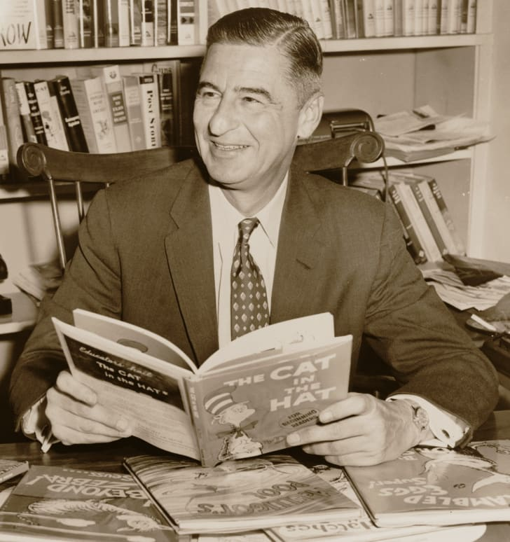 Ted Geisel (Dr. Seuss) seated at a desk covered with his books