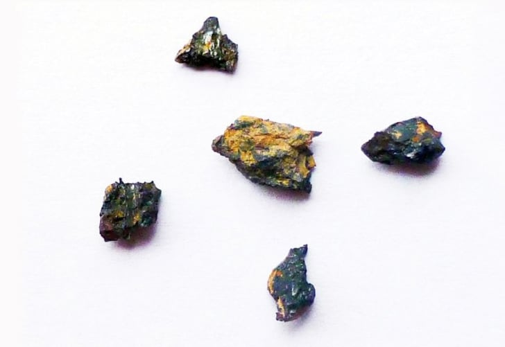 Five rocks on an off-white background