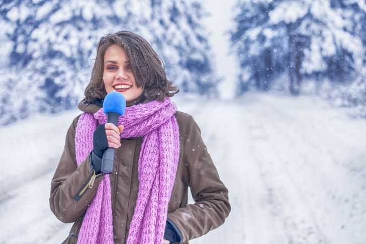 A young TV weatherperson in a snowy scene