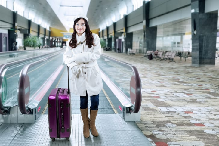 A woman in a winter coat and gloves stands in an airport with her suitcase.