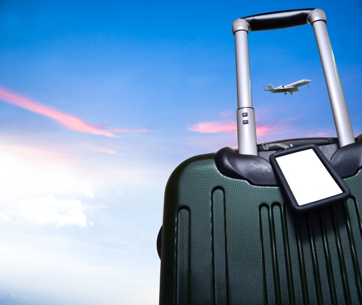 A closeup of a suitcase in front of a blue sky with a plane flying by.