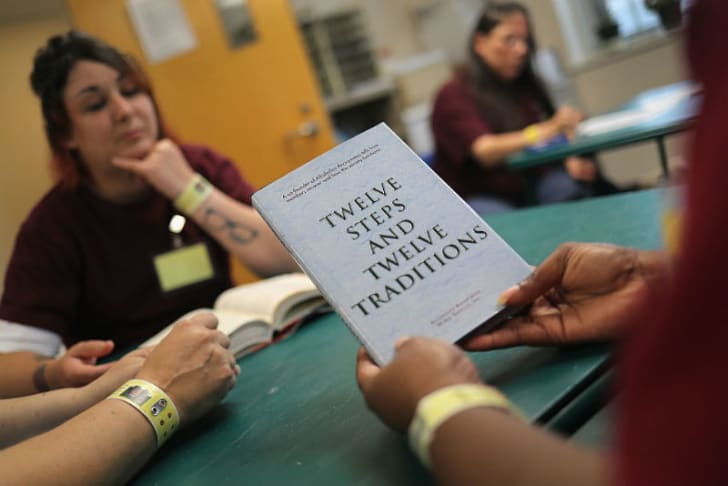 A prison inmate holds up a self-help book