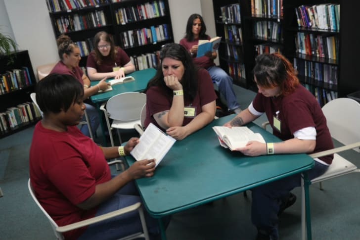 Inmates at a women's prison read books in the library
