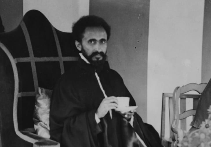 Haile Selassie sitting in a chair drinking tea.