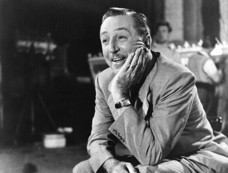 Walt Disney sitting in a chair.