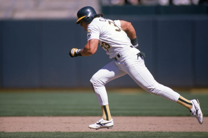 Jose Canseco #33 of the Oakland Athletics runs between the bases during a 1988 MLB season game at Oakland-Alameda County Coliseum in Oakland, California.