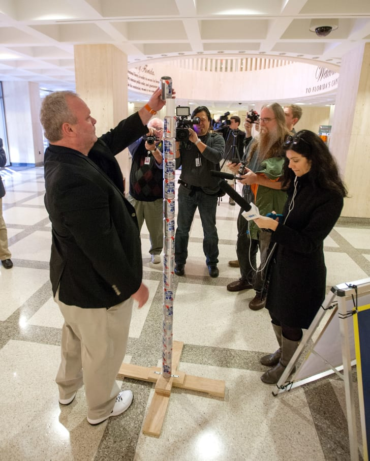 Chaz Stevens from Deerfield Beach, Florida assembles his Festivus pole out of beer cans in the rotunda of the Florida Capitol as the media looks on December 11, 2013 in Tallahassee, Florida