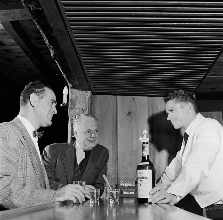 Men gathered around a bartender, 1950