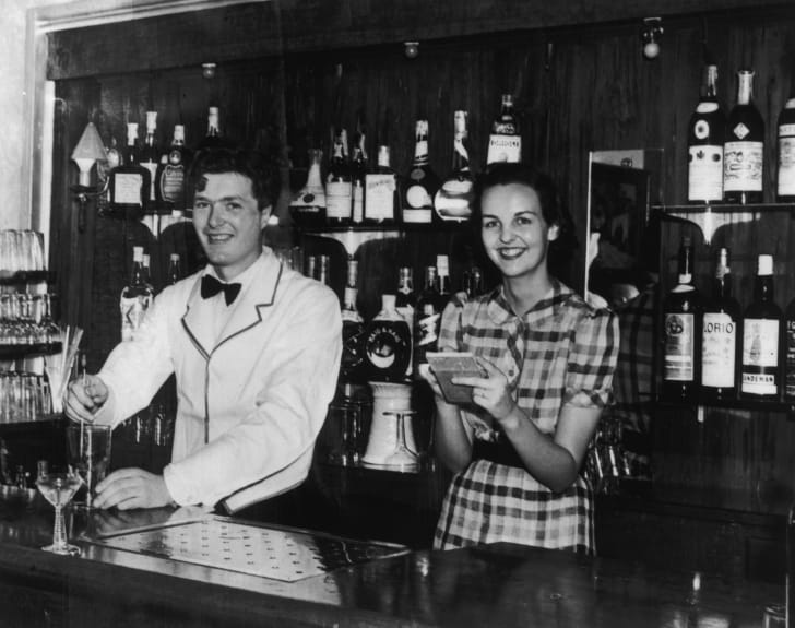 Jessica Mitford with her husband Esmond Romilly behind the bar of the Roma Restaurant in Biscayne Bay, 1940