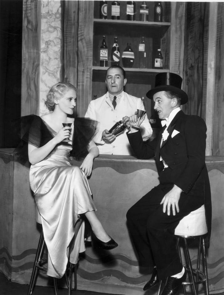 A smartly-dressed drunkard chats to a young lady at a bar in a theatre scene from 1933