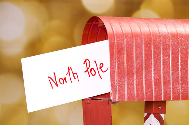 An evelope that reads 'North Pole' sticks out from a red mailbox.