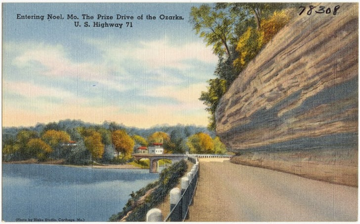 A vintage postcard shows a highway leading into the town of Noel, Missouri.