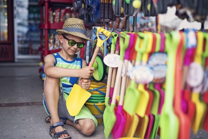 Little boy shops for a beach shovel