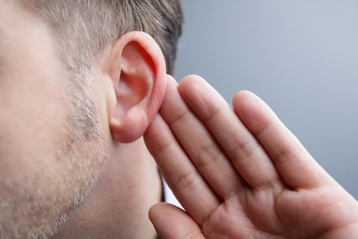 A man's hand next to his ear.