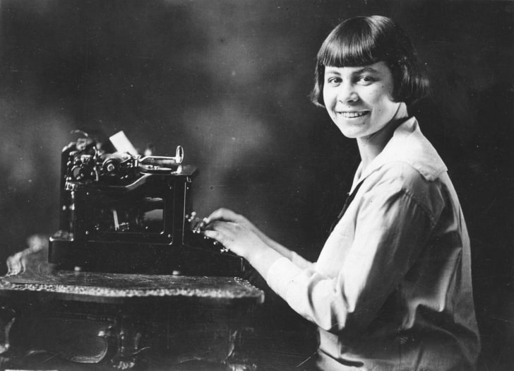 Woman sitting at a typewriter.