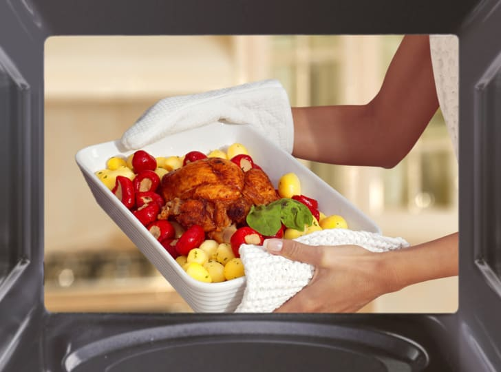 A woman holds up a baking dish with meat and potatoes in front of a microwave.