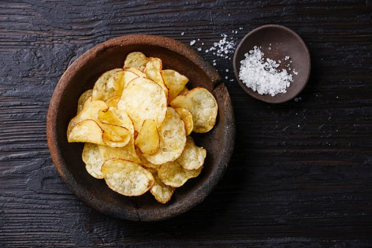 Chips in a bowl next to a small bowl of salt