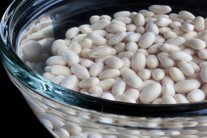 White beans soaking in a glass bowl