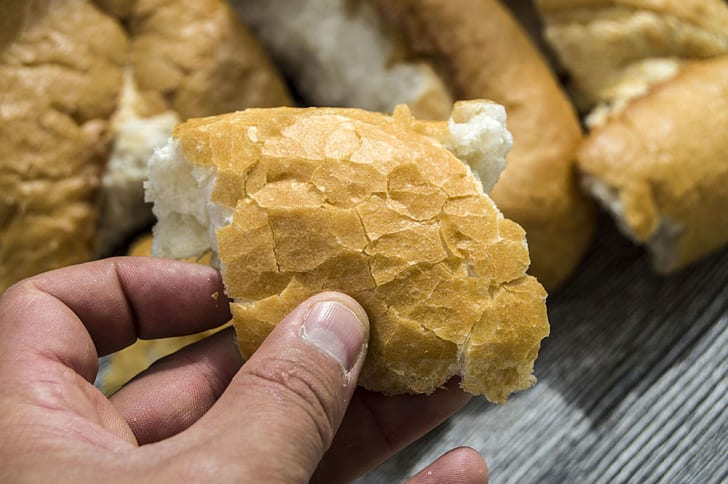 A hand holds up a piece of bread.