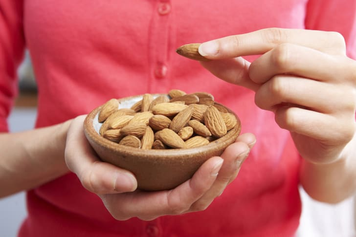 A woman picks up an almond from a bowl.