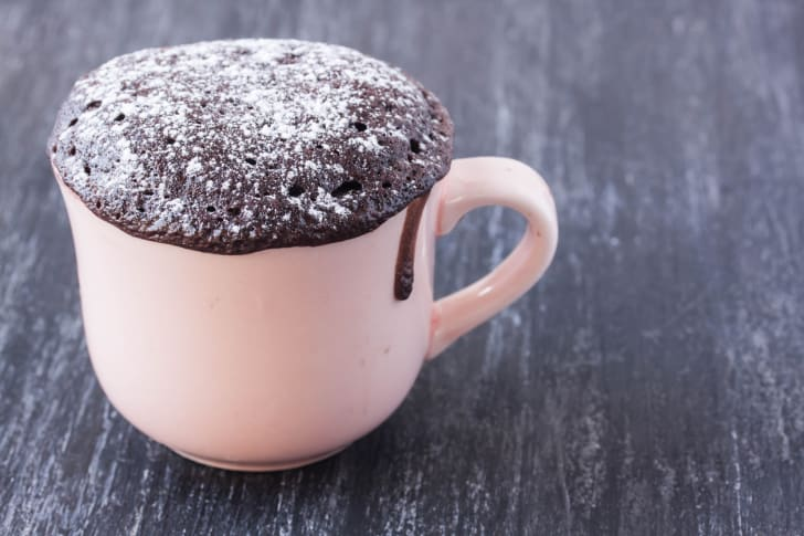A chocolate cake dusted with powdered sugar in a white mug