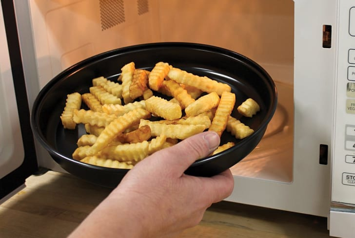 A man puts french fries in the microwave on a crisper tray.