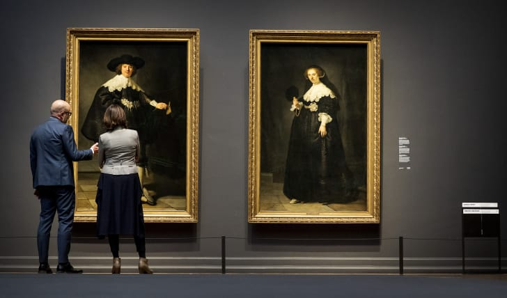Two visitors look at Marten and Oopjen, two Rembrandt portraits of a wedding couple