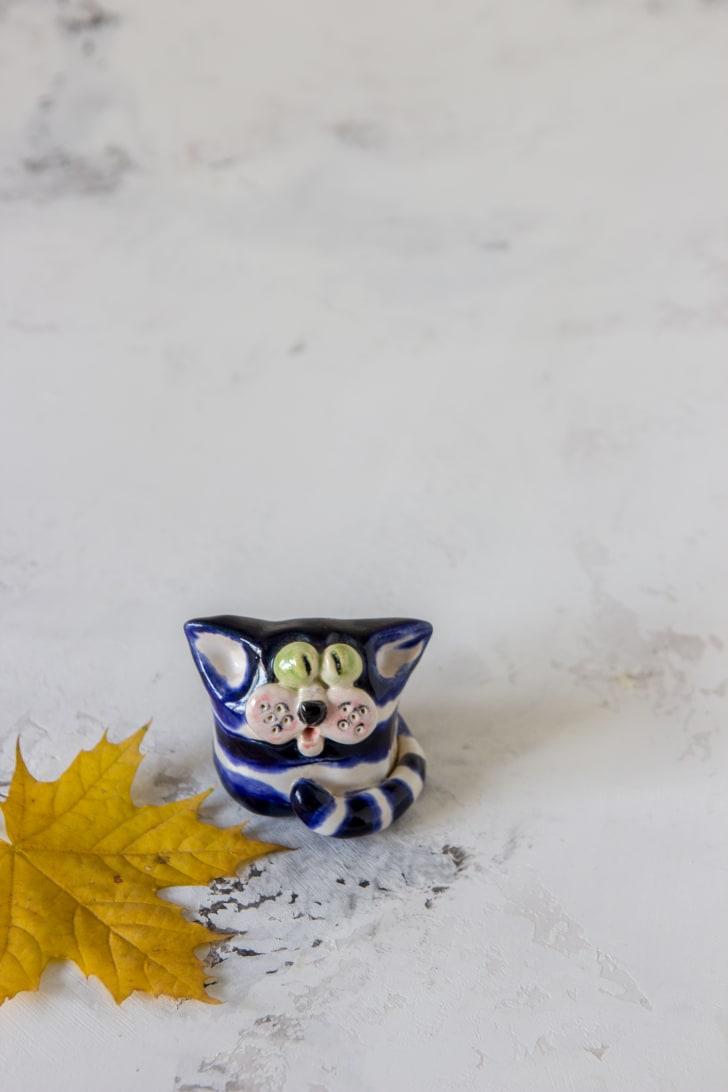 Porcelain cat figure and leaf