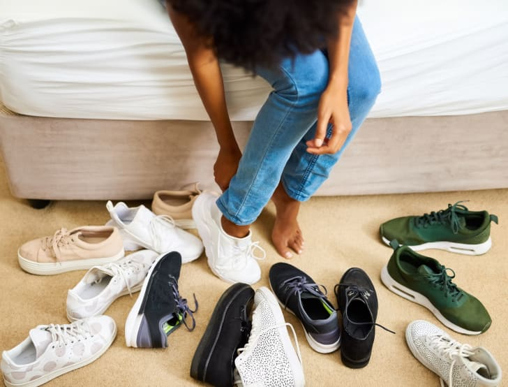 Woman sitting on bed trying on shoes from pile