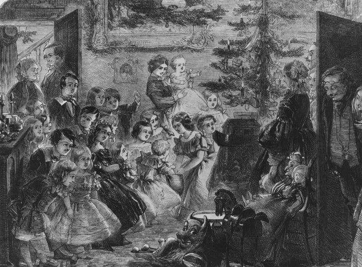 An illustration, circa 1858, of a family around a Christmas tree lit by candles.