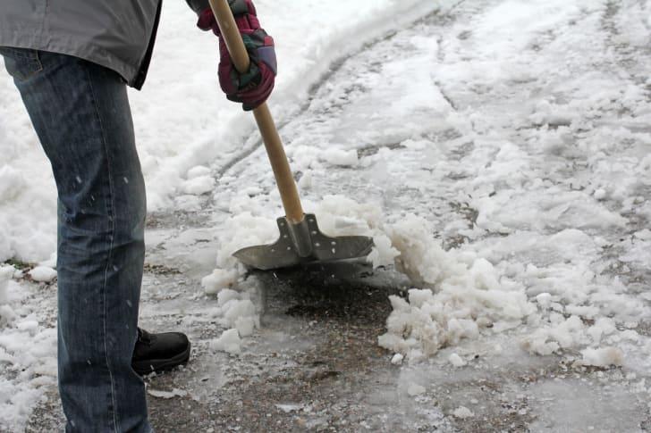 A man shoveling slushy snow in a driveway.