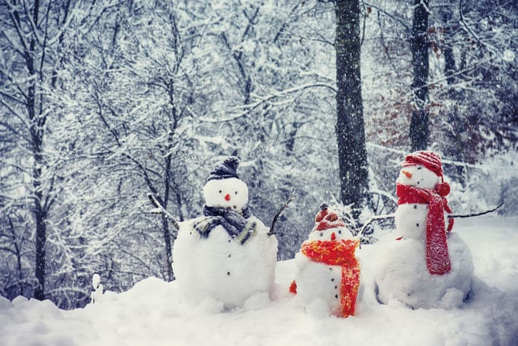 Three snowmen wearing bright scarves and hats.