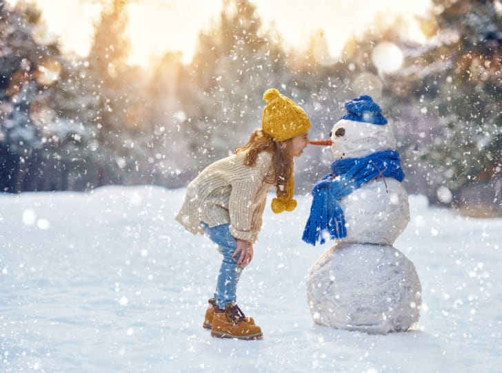 A little girl rubbing her nose on the carrot nose of a snowman while snow falls.