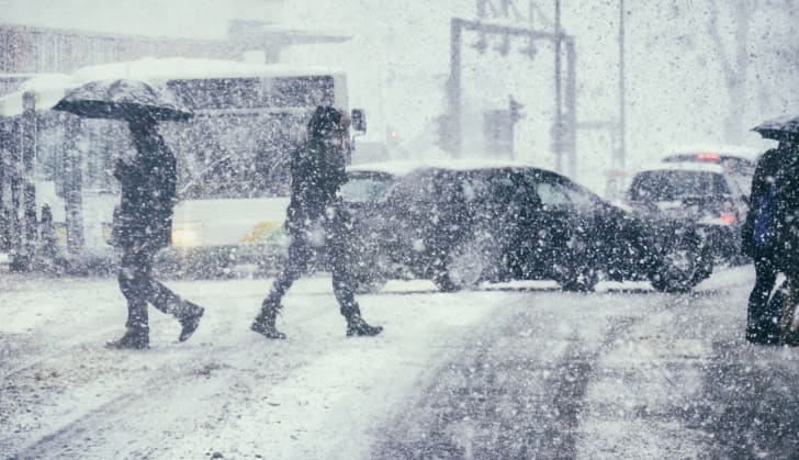 Pedestrians and cars in the snow.