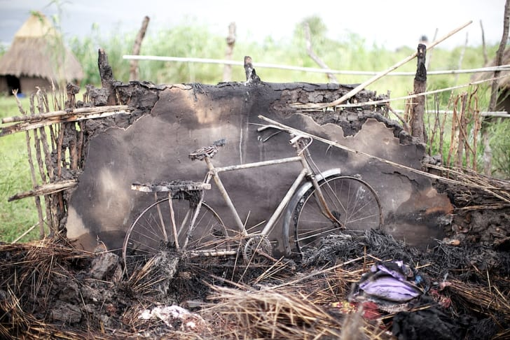 A burned house and bicycle in South Sudan.
