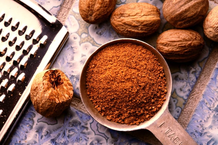 A tablespoon of grated nutmeg on a table surrounded by whole nutmegs and a grater.