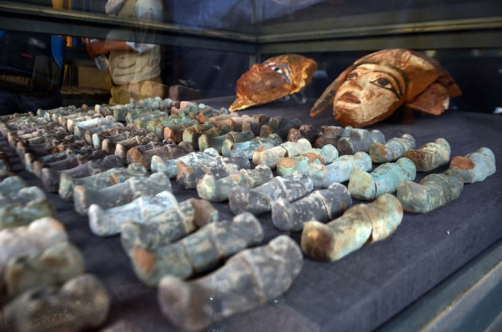 Ancient Egyptian wooden funerary masks and small statuettes found in and retrieved from the newly discovered 'Kampp 150' tomb at Draa Abul Naga necropolis in Luxor, Egypt.