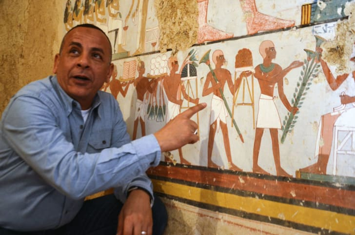 Mustafa al-Waziri, director general of Luxor's Antiquities, points at an ancient Egyptian mural found at the newly discovered 'Kampp 161' tomb at Draa Abul Naga necropolis.
