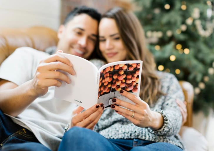 Two people looking at a photo book from Chatbooks