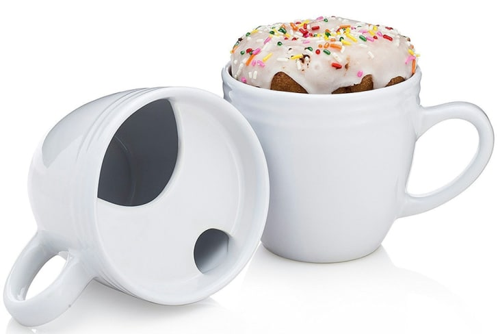 A coffee mug lies on its side to reveal a platform to hold a donut, while another sits with a donut on top nearby.